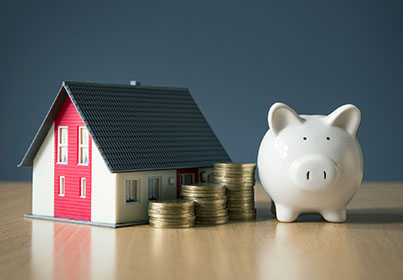 tiny house next to a piggy bank with stacks of coins in the middle