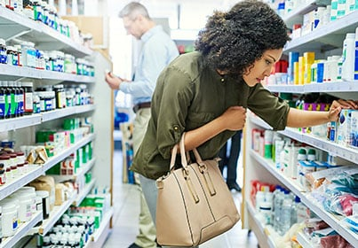 woman in pharmacy looking at an item on a shelf