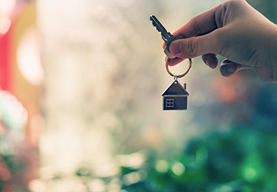 person holding keyring with house shaped key chain